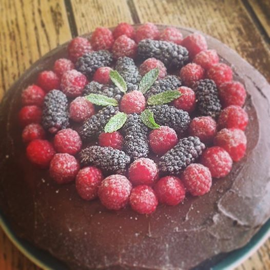 Vegan and gluten free chocolate cake with a berry, mint and creamy chocolate topping